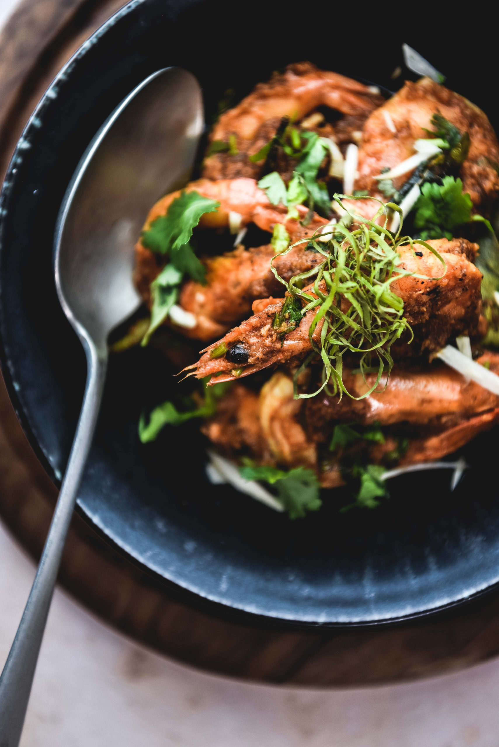 Prawns, silver spoon, black plate and wooden disk